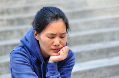 stressed woman sitting on the steps of a building with her chin in her hand