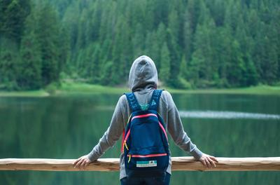Picture of person with a backpack and hoodie from the back facing a lake and trees