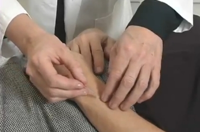 Acupuncturist's hands inserting needle on patient's arm