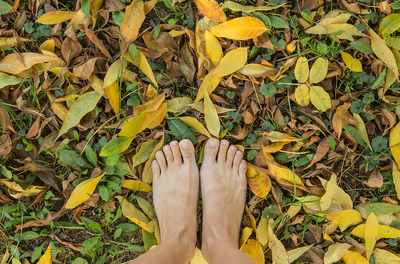 Two bare feet standing in dry yellow leaves