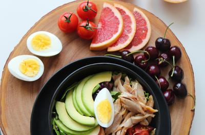 plate of colorful foods, including avocado, grapefruit, tomatoes, egg, and cherries