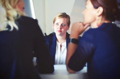 woman listening to two others speak in a meeting