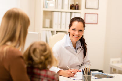 smiling white female doctor speaking with a child and adult in her office