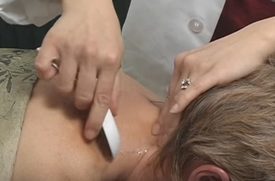 hands spreading hot oil on a patient's neck