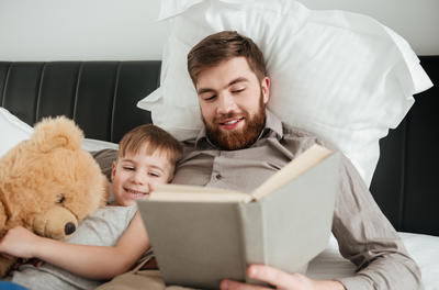 Photo of little boy lies at home in bed hugging a toy bear with his bearded father reading fairytale book.