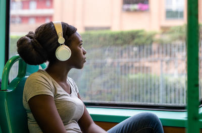 young black woman thinking traveling and listening to large headphones on a train