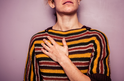 woman in colorful sweater with her hand on her chest