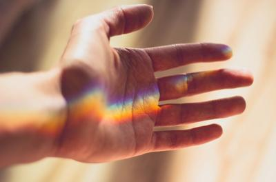 hand with rainbow light reflected