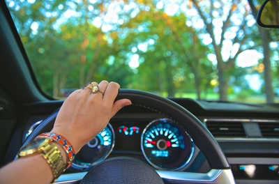 hand with bracelets and rings holding the steering wheel of a car