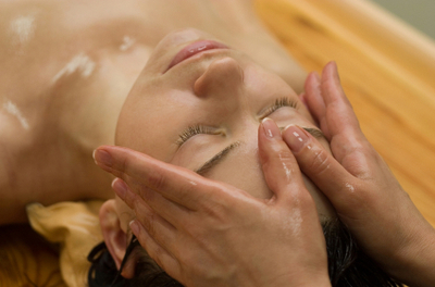 woman getting oil rubbed onto her forehead