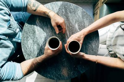 birds-eye view of two people with coffee cups at a small table