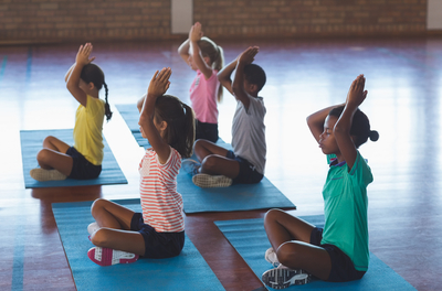 Group of five children doing yoga poses in a gym