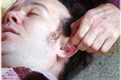 close up of man getting ear reflexology while he sleeps