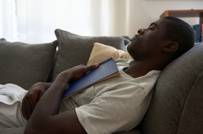 man napping on a couch with a book open on his chest