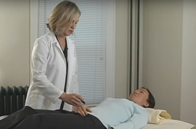 healthcare practitioner standing next to a woman lying on a table