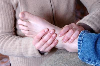 reflexologist hands on a patient's foot