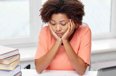 college student sitting at desk with her head in her hands next to stack of books