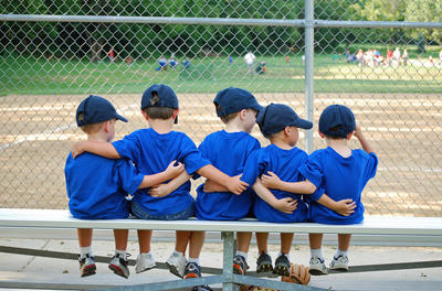 Group of five kids in matching uniforms sitting on a bench in the dugout, with their arms around each other