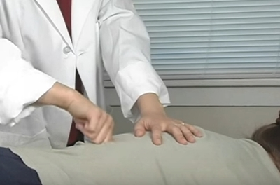hands massaging a back
