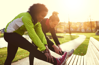 two women in running clothes stretching their legs by a park bench