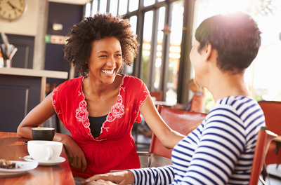 Two women happily talking in coffee shop
