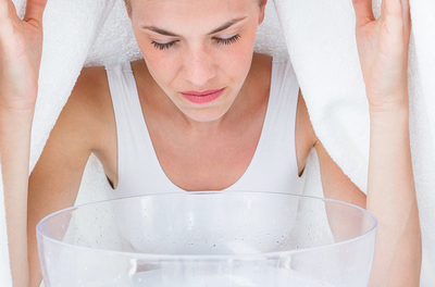 woman with a towel draped over head, inhaling steam from a bowl
