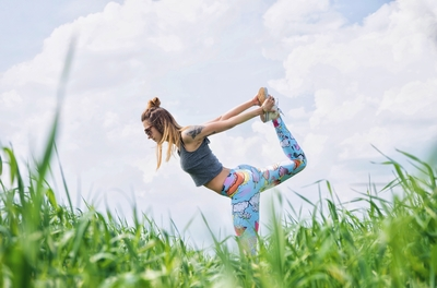 woman with colorful exercise pants stretching outside in the grass