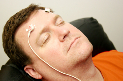 Man in orange shirt leaning back in a chair with two electrodes on his forehead
