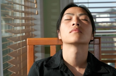 Woman leaning back in chair with her eyes closed